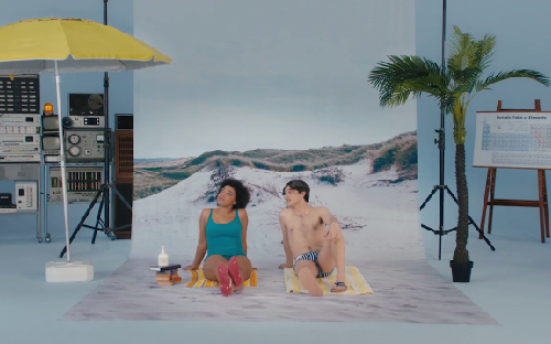 A woman and a man sitting in bathers at a beach setting within a studio.