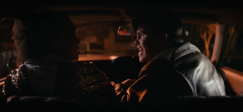 A man yelling at a woman in the car, grabbing her arm. She looks startled.